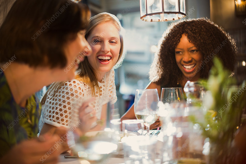 Laughing women friends talking and dining