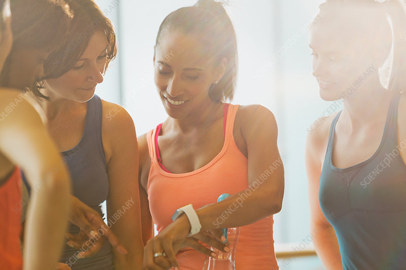 Women looking at smart watch in sunny gym studio