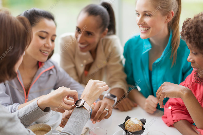 Smiling women friends looking at smart watches