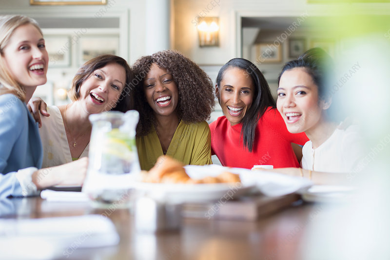 Portrait laughing women friends dining