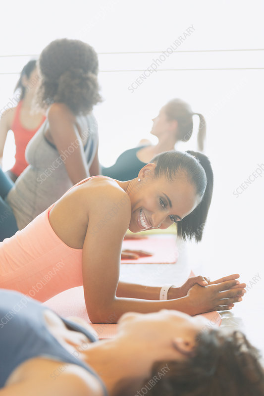 Smiling women talking on yoga mats