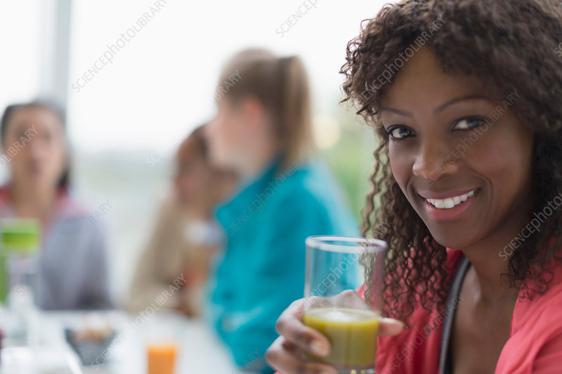 Portrait smiling woman drinking smoothie