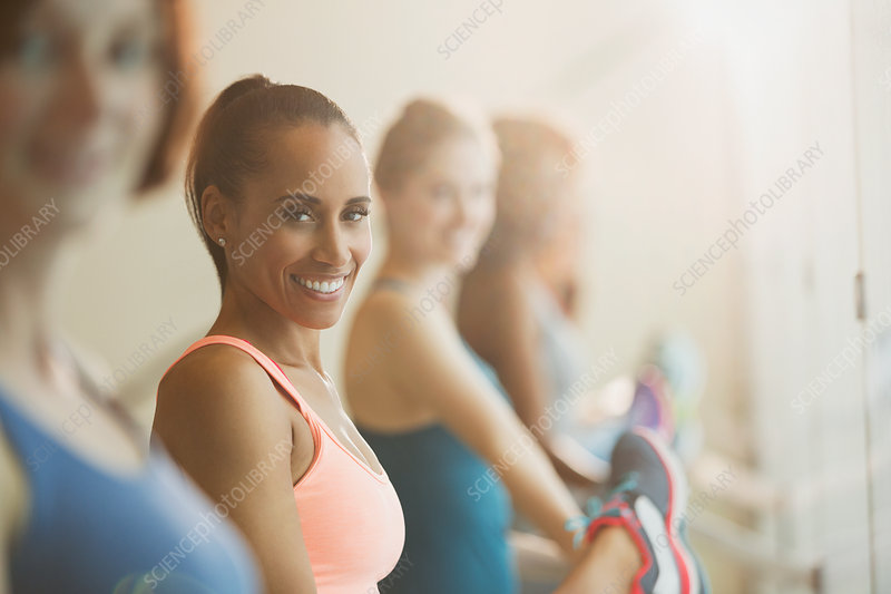 Portrait smiling women stretching legs at barre