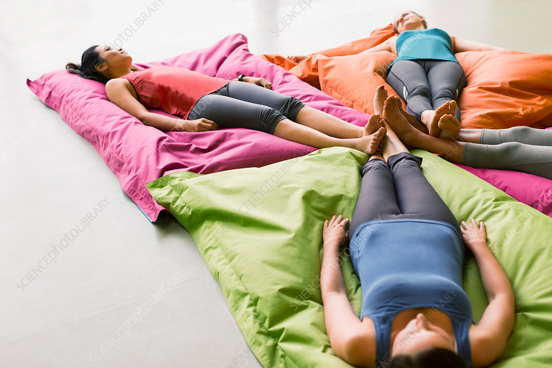 Women laying on cushions in yoga gym studio