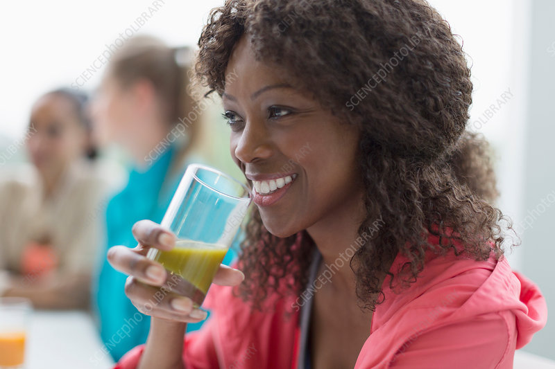Smiling woman drinking healthy green smoothie