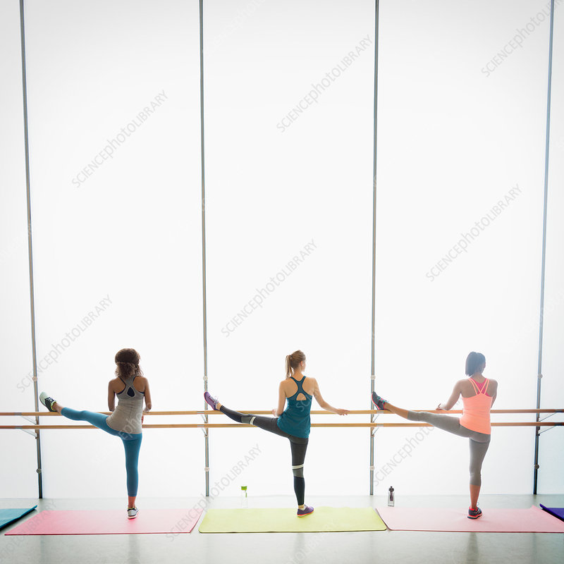 Women stretching legs at barre