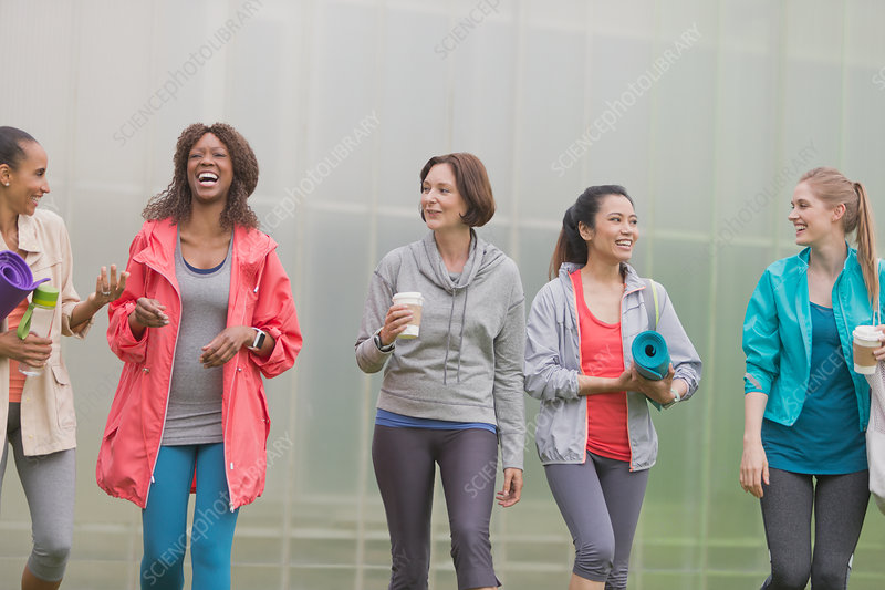 Smiling women walking with yoga mats and coffee
