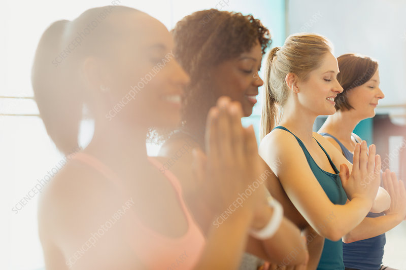 Serene women practicing yoga with hands