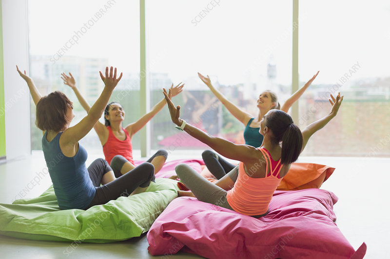 Women leaning with arms raised on cushions