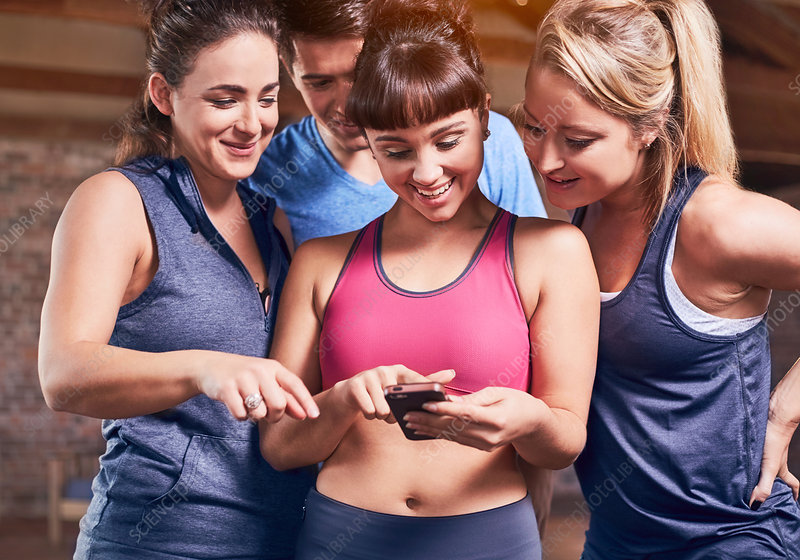 Young women and man in sports clothing texting