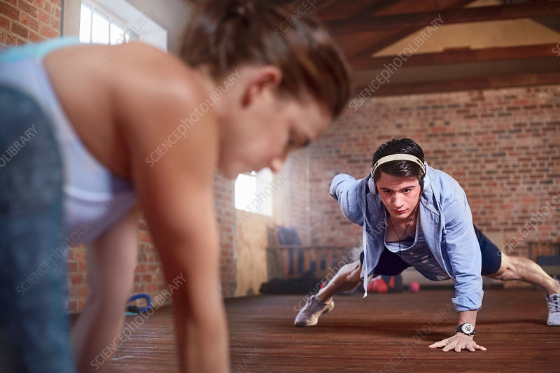 Young man with headphones doing one-arm push-ups