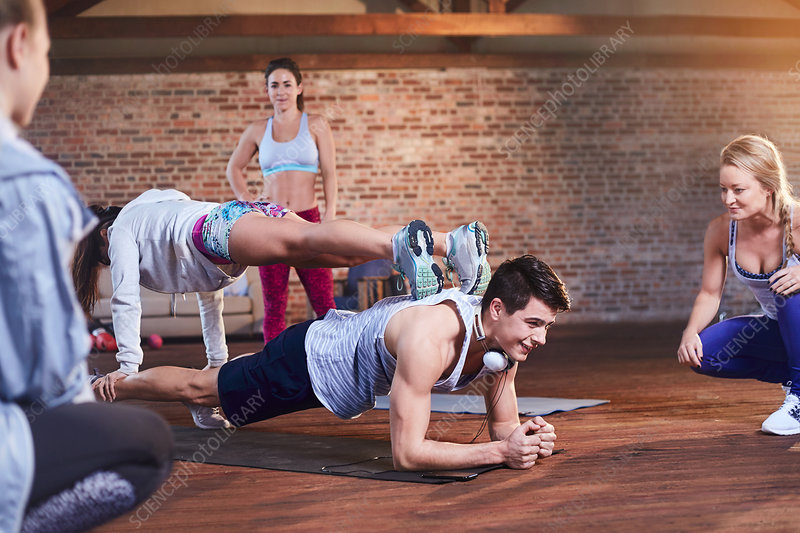Young man and woman practicing stacked plank pose