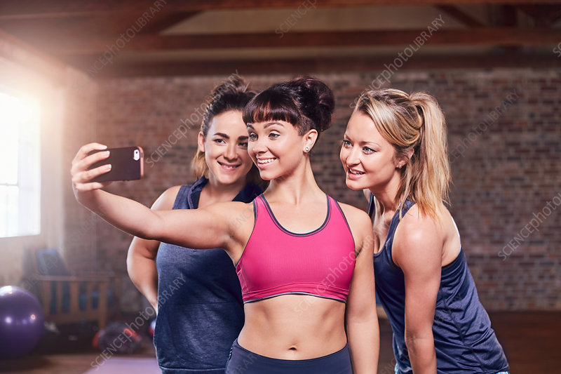 Fit young women in sports clothing taking selfie