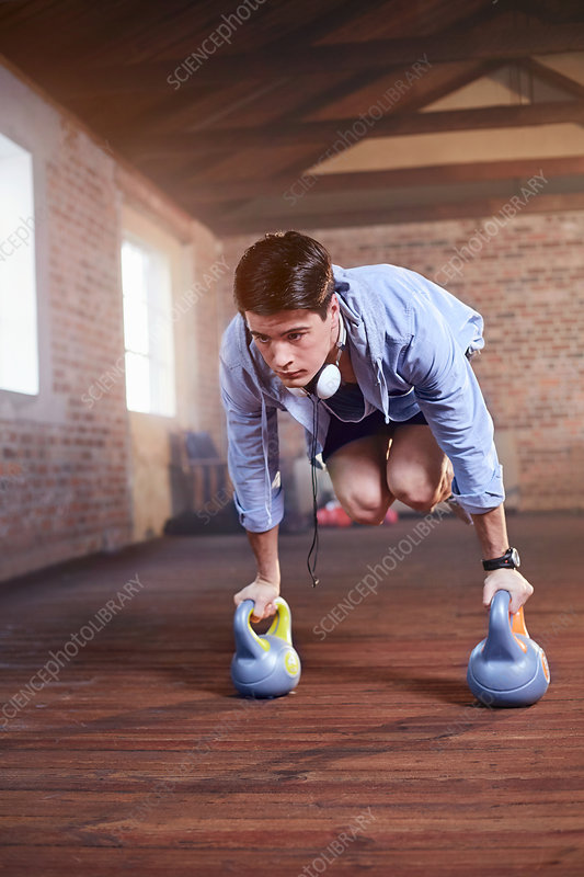 Young man jumping with kettle bells in gym studio