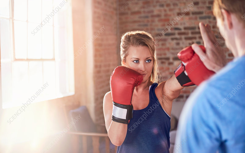 Young female boxer practicing boxing with trainer