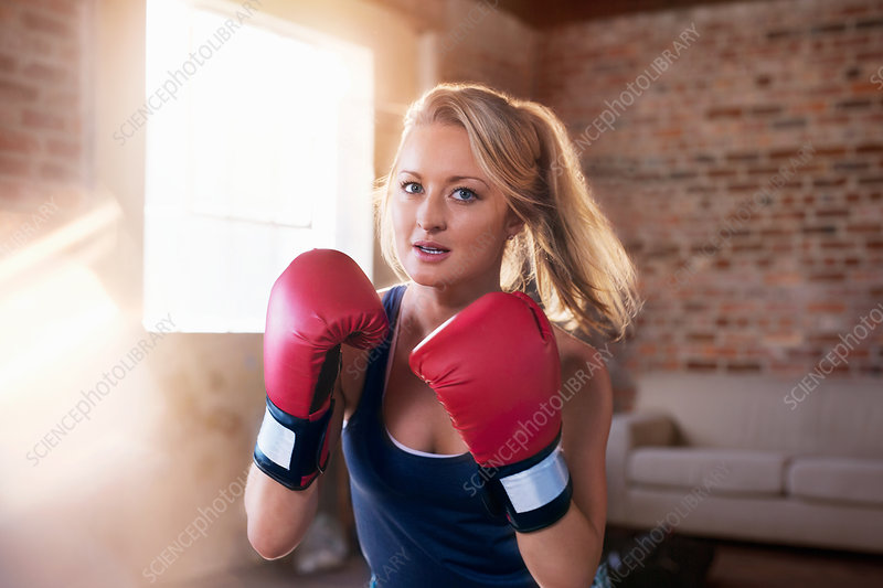 Portrait tough young woman boxing in studio