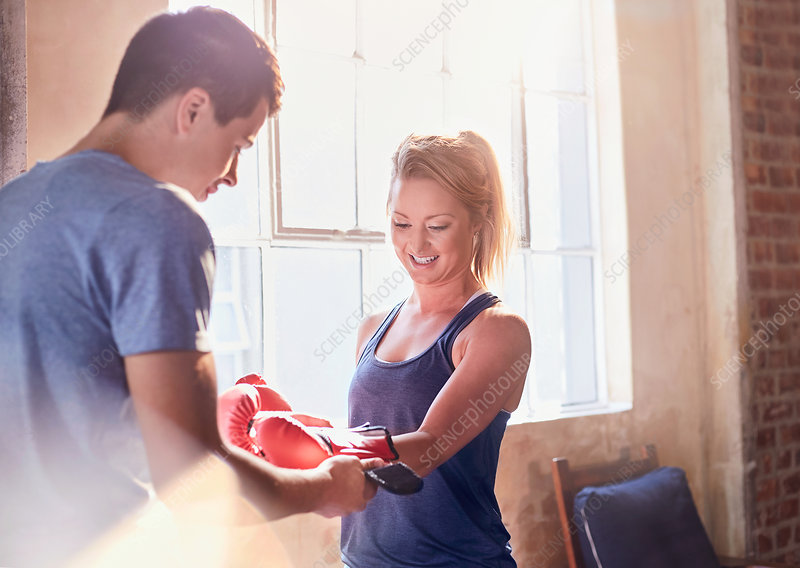 Trainer helping young female boxer