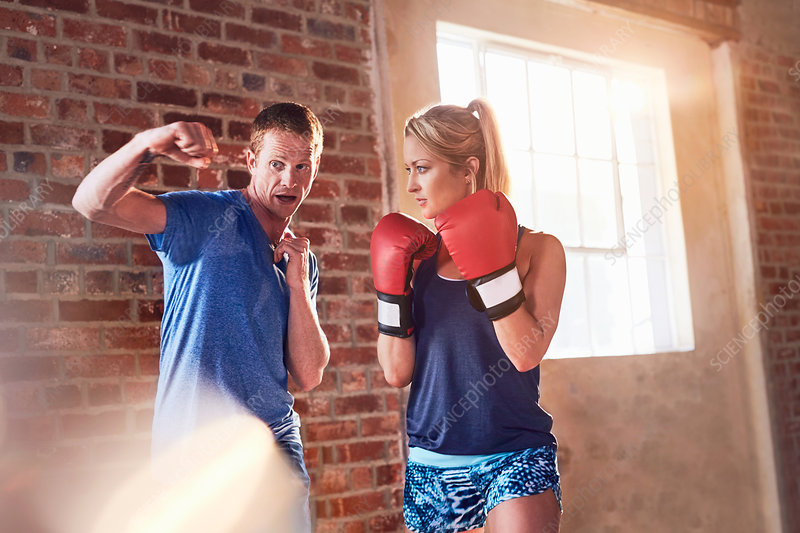 Trainer teaching young woman boxing in studio