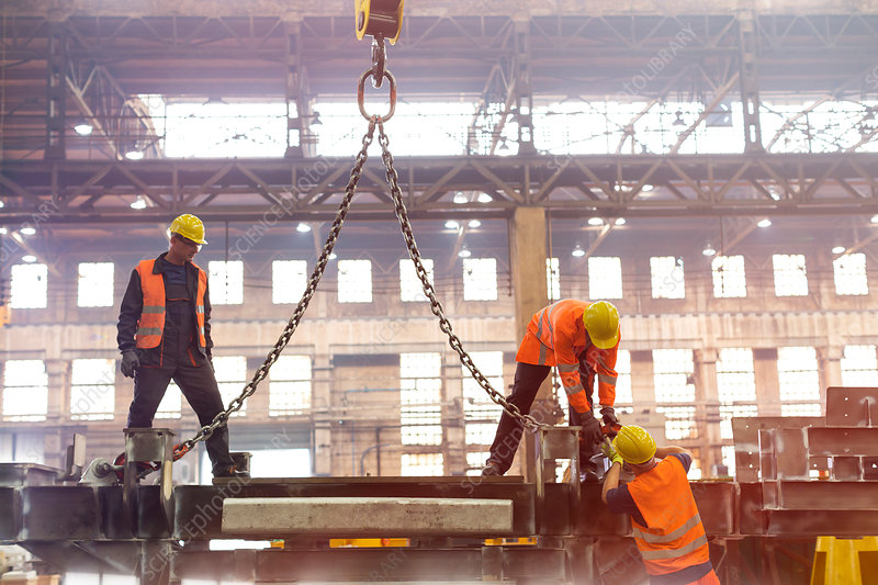 Steel workers fastening crane chain in factory