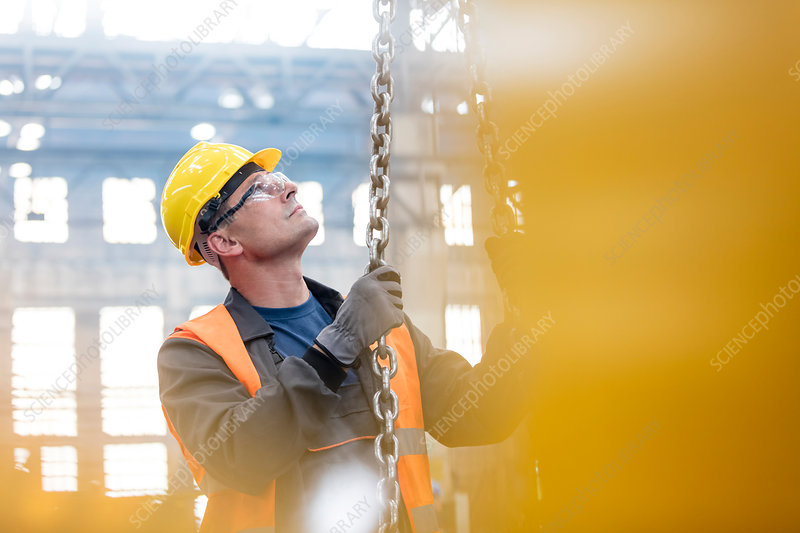 Steel worker holding chain in factory