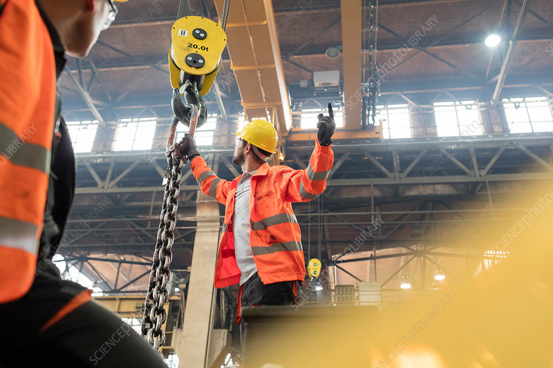 Steel workers fastening chain to crane in factory