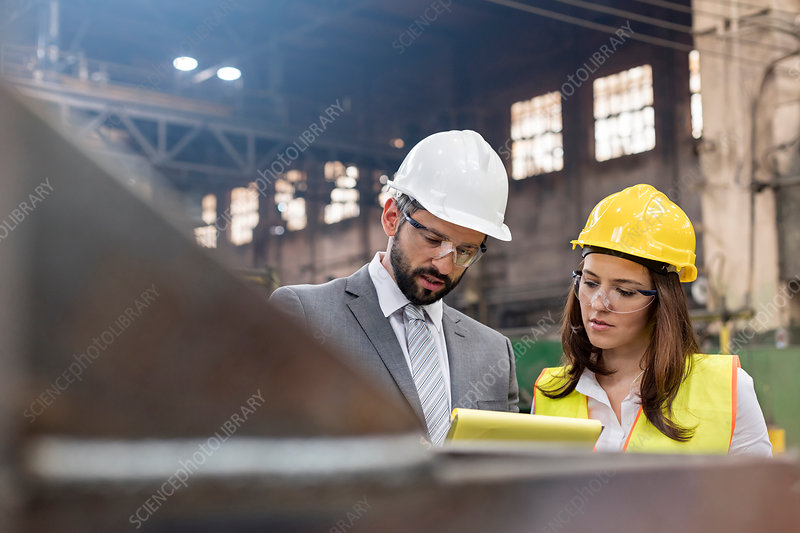 Manager and female steel worker meeting in factory