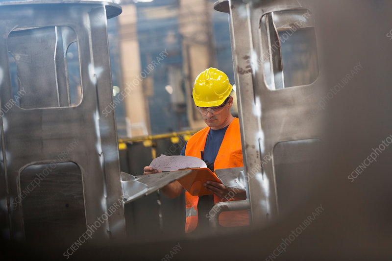 Steel worker reviewing paperwork in factory