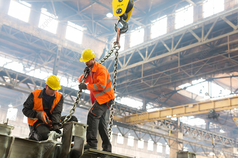 Steel workers fastening crane chain to steel