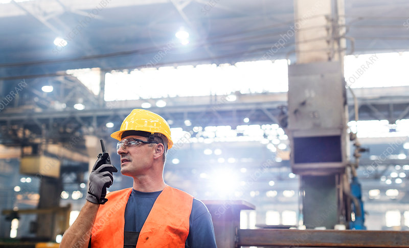 Steel worker using walkie-talkie in factory