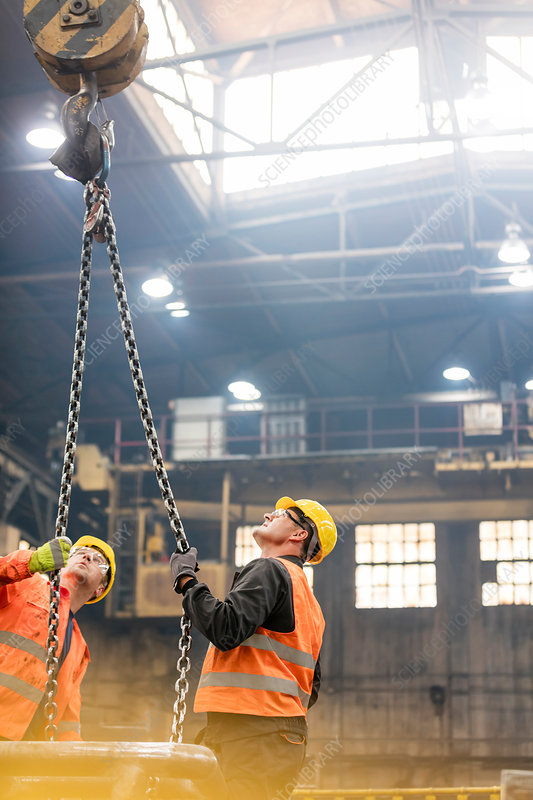 Steel workers looking up at crane chain in factory