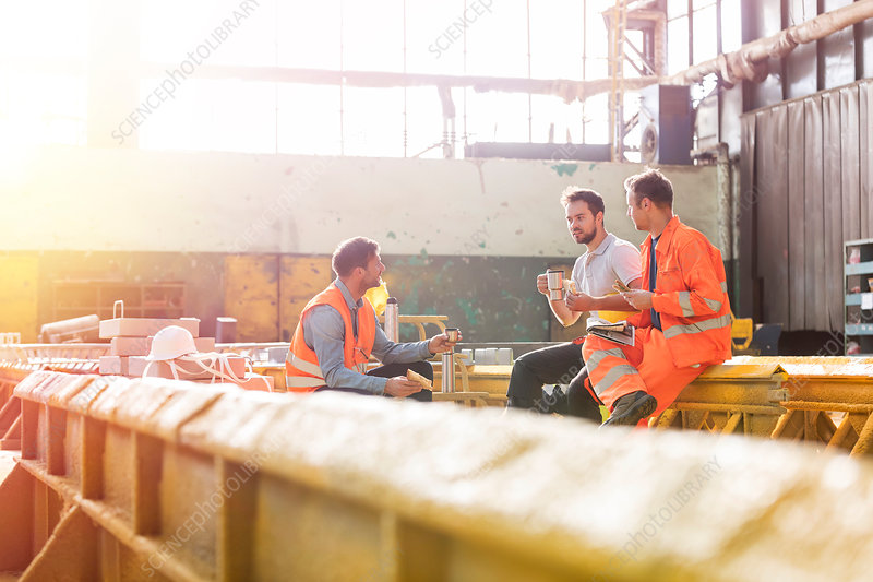 Steel workers enjoying lunch break in factory
