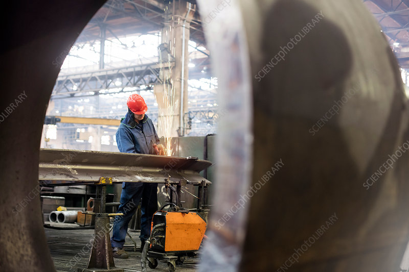 Welder using welding torch in steel factory