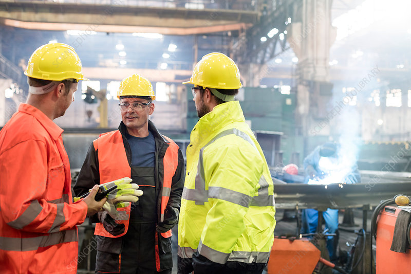 Steel workers talking in factory