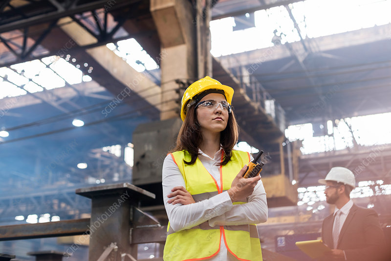 Female steel worker with walkie-talkie in factory