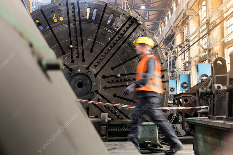 Steel worker walking in factory