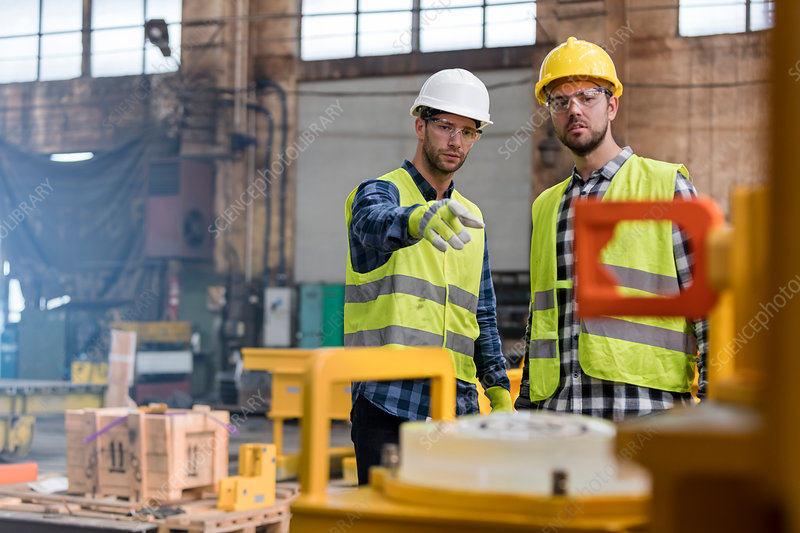 Steel workers talking and pointing in factory