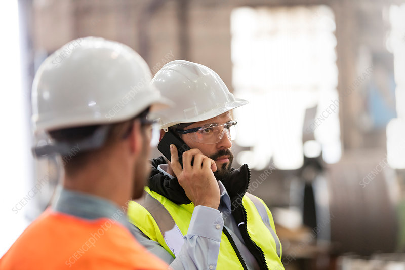 Steel workers talking on cell phone in factory