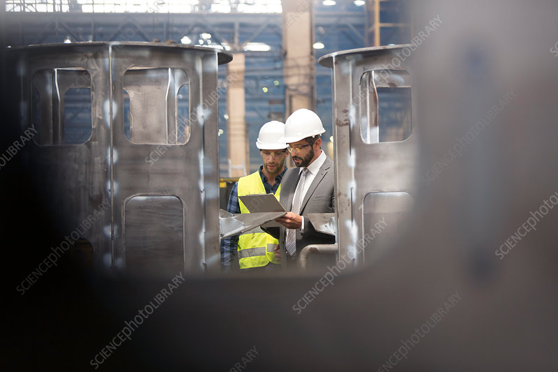 Manager and steel worker with clipboard meeting