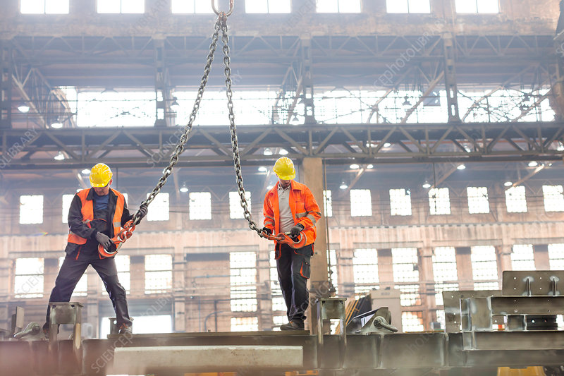 Steel workers with crane hooks in factory