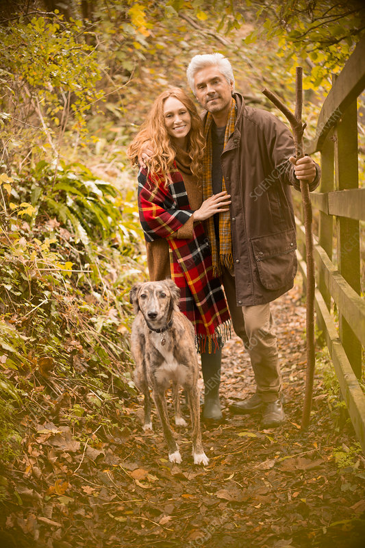 Portrait smiling couple with dog and walking stick