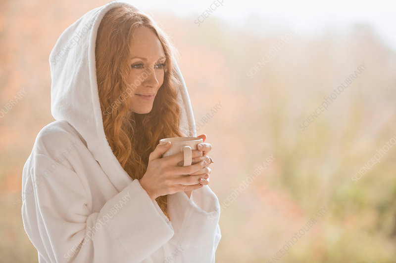 Serene woman in hooded bathrobe drinking coffee