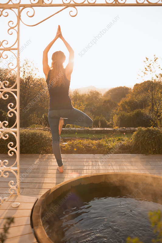 Woman practicing yoga tree pose on patio