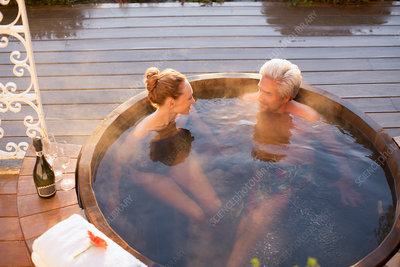 Couple in hot tub drinking champagne on patio