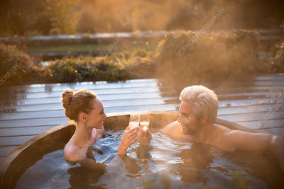 Couple toasting champagne glasses in hot tub
