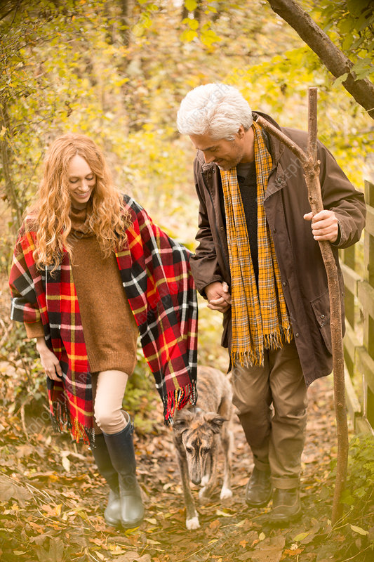Couple with dog and walking stick in autumn woods