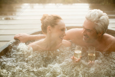 Smiling couple drinking champagne in hot tub
