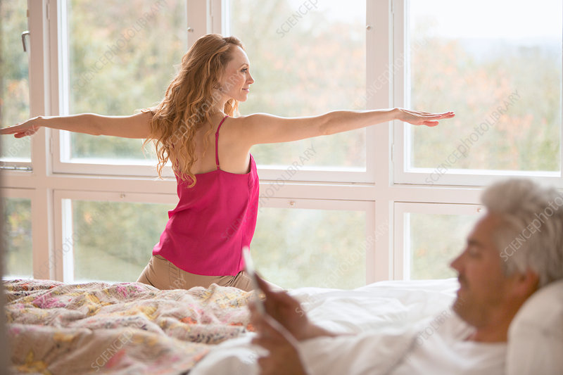Woman practicing yoga pose and husband in bed