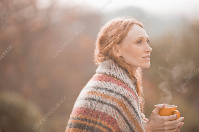 Serene woman wrapped in blanket drinking coffee