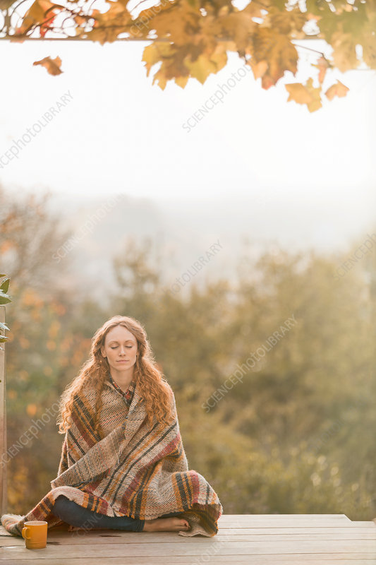 Serene woman wrapped in blanket meditating