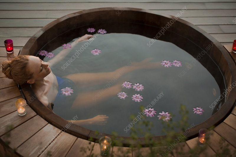 Serene woman in hot tub with flowers and candles